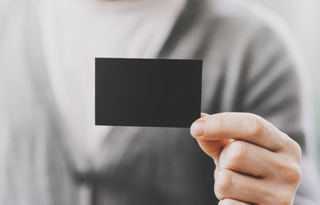 private information: Man wearing casual shirt and showing empty black business card. Blurred background. Ready for private information. Horizontal mockup, fim effects.