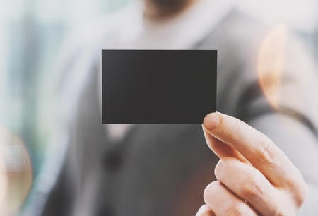 private information: Man wearing casual shirt and showing blank black business card. Blurred background. Ready for private information. Horizontal mockup, film effect. Stock Photo