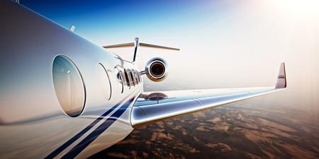 Foto van Witte Luxe Generisch Ontwerp Privé Jet Vliegen In Blauwe Hemel Bij Zonsondergang.Uninhabited Desert Mountains Background.Business Travel Picture.Horizontal, Film Effect. 3D-weergave