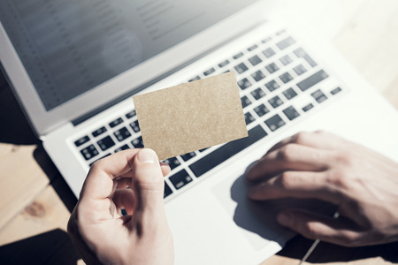 private information: Photo Man Showing Blank Craft Business Card and Using Hand Modern Laptop Blurred Background. Mockup Ready for Private Information. Sunlight Reflections Screen Gadget. Horizontal mock up