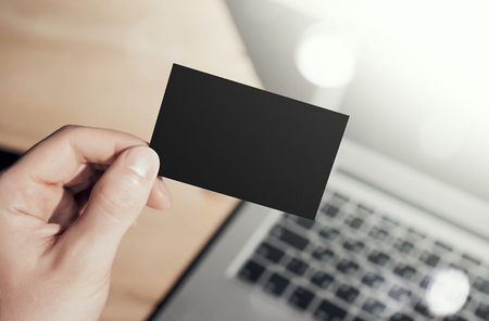private information: Closeup Photo Man Showing Blank Craft Business Card and Using  Modern Laptop Blurred Background. Mockup Ready for Private Information. Sunlight Reflections Screen Gadget. Horizontal mock up Stock Photo