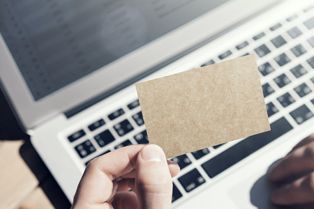 private information: Closeup Photo Man Showing Blank Craft Business Card and Using Hand Modern Laptop Blurred Background. Mockup Ready for Private Information. Sunlight Reflections Screen Gadget. Horizontal mock up
