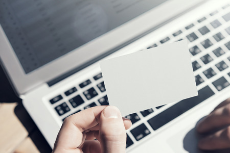 private information: Closeup Photo Man Showing Blank White Business Card and Using  Modern Laptop on Wood table Blurred Background. Mockup Ready for Private Information. Sunlight Reflections Gadget. Horizontal mock up