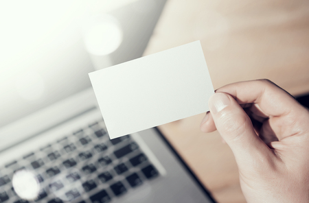 private information: Closeup Photo Man Showing Blank White Business Card and Using  Modern Laptop on Wood table Blurred Background. Mockup Ready for Private Information. Sunlight Flares Gadget. Horizontal mock up