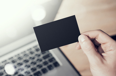 private information: Closeup Photo Man Showing Blank Black Business Card and Using  Modern Laptop on Wood table Blurred Background. Mockup Ready for Private Information. Sunlight Flares Gadget. Horizontal mock up