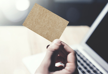private information: Closeup Image Man Showing Blank Craft Business Card and Using  Modern Laptop on Wood table Blurred Background. Mockup Ready for Private Information. Sunlight Flares. Horizontal mock up Stock Photo