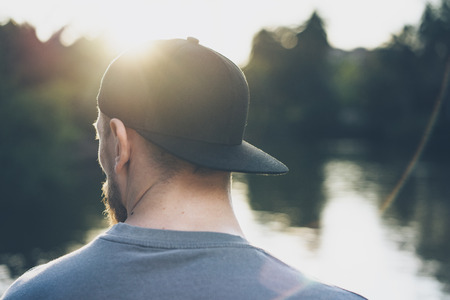 Photo Bearded Young Man Wearing Black Blank Cap. Green City Park Lake Background and Sunset effect. Back view. Horizontal Mockup.