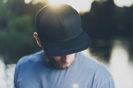 Foto bärtiger junger Mann tragen schwarze Blank Cap. Green City Park Lake Hintergrund und Sonnenuntergang Wirkung. Vorderansicht. Horizontal Mockup.