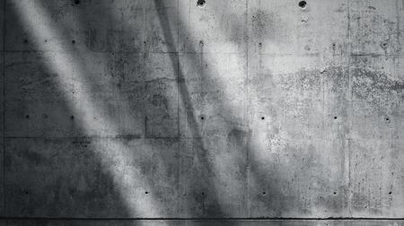Photo horizontale Mur en béton nu lisse et rugueux avec des rayons de soleil reflétant sur une surface sombre. Ombres douces. Contexte vide. Noir et blanc.
