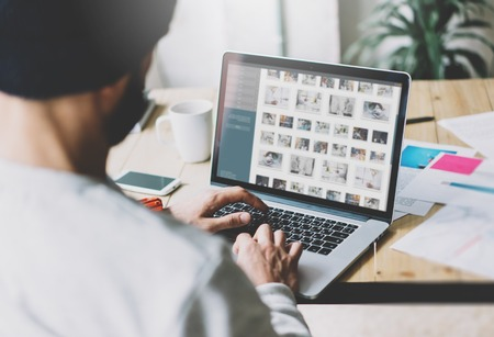 Photo bearded graphic designer working with new project modern loft. Contemprary notebook on wood table.  Images screen, hands typing keyboard. Freelance world. Blurred background Stock Photo