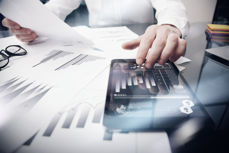Risk Management Work process.Photo Trader working Market Report Documents Touching Screen Tablet.Using Graphic Icons,Stock Exchanges Reports. Business Project Startup. Horizontal, .