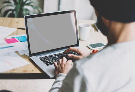 Diseñador barbudo de la foto que trabaja con el desván moderno del nuevo proyecto. Usando el ordenador portátil contemprary en la tabla de madera. Proceso creativo. Cierre la pantalla de la reflexión del cuaderno. Fondo borroso, efecto de la película, horizontal