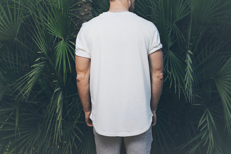 Photo Bearded Muscular Man Wearing White Blank t-shirt in summer time. Green huge palm Background. Back view. Horizontal Mockup.