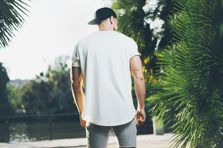 Photo Bearded Muscular Man Wearing White Blank t-shirt, snapback cap and shorts in summer time. Green City Garden Park Background. Back view. Horizontal Mockup.