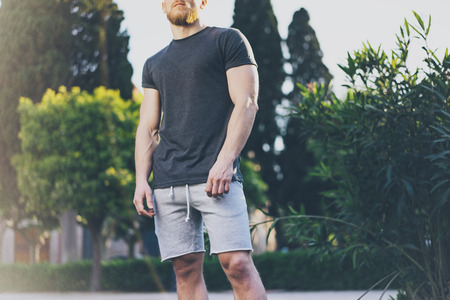 Photo Bearded Muscular Man Wearing Black Empty t-shirt and shorts in summer time vacation. Green City Garden Park Background. Front view. Horizontal Mockup. Stock Photo