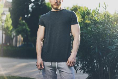 Imagen Hombre barbudo que desgasta muscular Negro Vacío camiseta y pantalones cortos en vacaciones de verano. Fondo Verde Garden City Park. Vista frontal. Prototipo horizontal