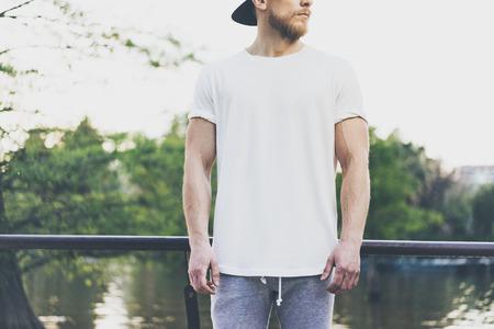 Foto Uomo muscolare barbuto indossando la maglietta vuota bianca, il cappello di snapback e i bicchierini in estate. Tempo di freddo vicino al lago. Green City Garden Park Sfondo tramonto. Vista frontale. Mockup orizzontale