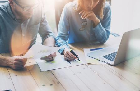 Coworking Sitzung. Bild junge kreative Crew mit neuen Startup-Projekt arbeiten. Desktop auf Holztisch. Ideenpräsentation, zu analysieren Marketing-Pläne. Unscharfen Hintergrund, Lichteffekte, Filmeffekt
