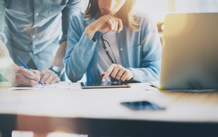 Sales Managers Working Modern Loft.Woman Showing Market Report Digital Tablet.Producer Department Work New Startup Project.Researching Process Wood Table.Horizontal.Burred Background.Film effect