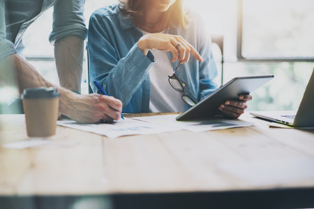 Sales Manager Arbeiten Modern Studio.Woman Zeige Marktbericht Digitale Tablet.Producer Abteilung arbeiten, um neue Startup Project.Researching Prozess Holz Table.Horizontal.Burred Background.Film Wirkung