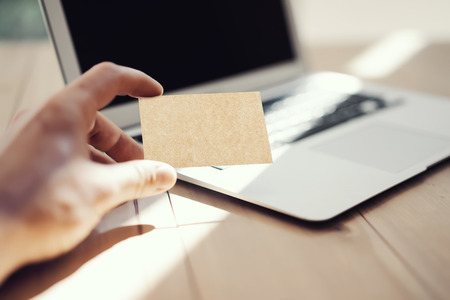 private information: Photo Man Showing Blank Craft Business Card and Using Modern Laptop Wood Table. Blurred Background. Mockup Ready for Private Information. Sunlight Reflections Surface Gadget. Horizontal mock up Stock Photo