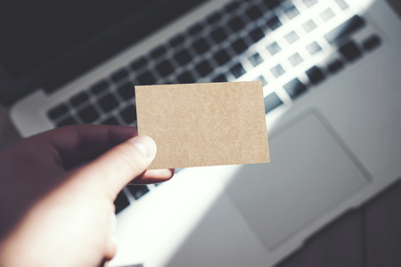private information: Photo Man Showing Blank Craft Business Card and Using Modern Laptop Blurred Background. Mockup Ready for your Private Information. Sunlight Reflections Surface Gadget. Horizontal mock up Stock Photo