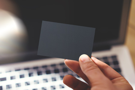 private information: Closeup Photo Man Showing Blank Black Business Card and Using Modern Laptop Blurred Background. Mockup Ready for Private Information. Sunlight Reflections Surface Gadget. Horizontal mock up Stock Photo