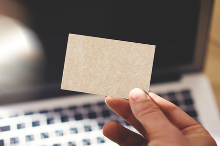 private information: Closeup Photo Man Showing Blank Craft Business Card and Using Modern Laptop Blurred Background. Mockup Ready for Private Information. Sunlight Reflections Surface Gadget. Horizontal mock up