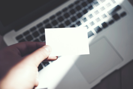 private information: Image Man Showing Blank White Business Card and Using Modern Laptop Blurred Background. Mockup Ready for Private Information. Sunlight Reflections Surface Gadget. Horizontal mock up