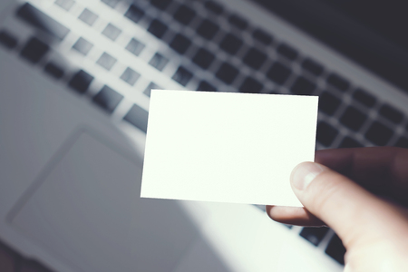 private information: Closeup Image Man Showing Blank White Business Card and Using Modern Laptop Blurred Background. Mockup Ready for Private Information. Sunlight Reflections Surface Gadget. Horizontal mock up Stock Photo