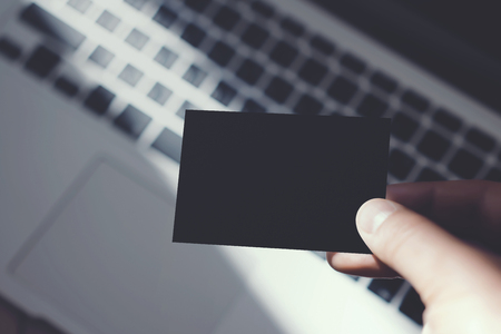 private information: Closeup Image Man Showing Blank Black Business Card and Using Modern Laptop Blurred Background. Mockup Ready for Private Information. Sunlight Reflections Surface Gadget. Horizontal mock up