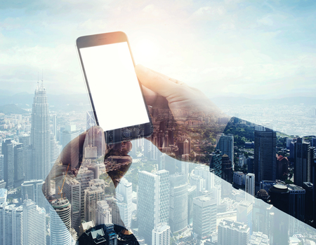 panoramic business: Double exposure photo modern smartphone holding male hands. Panoramic view contemporary city and clouds background. White blank screen ready for your business information.Horizontal mockup