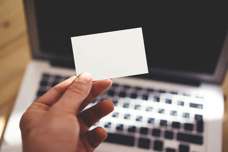 private information: Photo Man Showing Blank White Business Card and Using Modern Laptop Blurred Background. Mockup Ready for Private Information. Sunlight Reflections Surface Gadget. Horizontal mockup Stock Photo