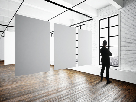 Businessman Modern museum expo loft interior.Open space studio.Empty white canvas hanging.Wood floor,bricks wall,panoramic windows.Blank frames ready for bussiness information.Horizontal mockup