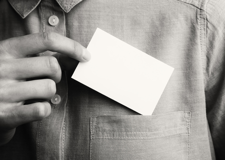 private information: Man showing empty business card hand. Adult businessman takes out blank Card from the pocket of his shirt. Ready for your private information. Black and White. Horizontal mockup