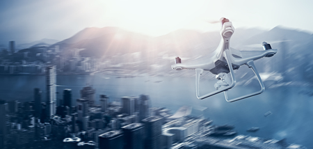 Photo White Matte Generic Design Remote Control Air Drone with action camera Flying Sky under City. Modern Megapolis Background. Wide, side angle view. Motion blur Effect. 3D rendering
