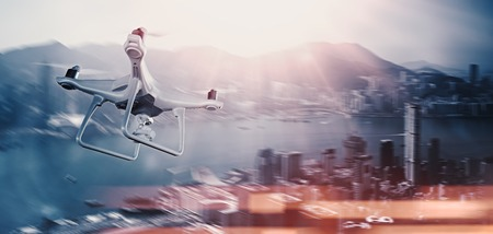 megapolis: Photo White Matte Generic Design Remote Control Air Drone with action camera Flying Sky under City. Modern Megapolis Background. Wide, side view. Motion Blur,Bokeh Effect. 3D rendering Stock Photo
