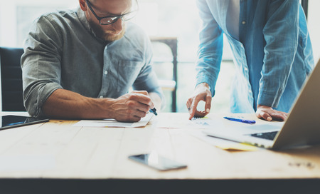 contabilidad: Los compañeros de trabajo lluvia de ideas en equipo moderno gestor de office.Project con gafas, el hombre hace notas marker.Young equipo de negocios que trabajan con la madera puesta en marcha studio.Laptop table.Blurred, efecto de película. Foto de archivo