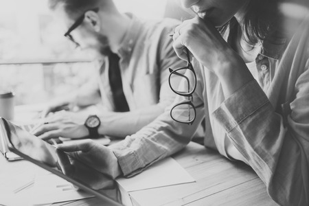 business finance: Coworkers team brainstorming process in modern office.Project manager thinking,holding glasses female hand.Young business crew working with startup studio.Laptop table,using tablet.Black White.Blurred