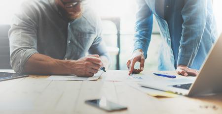 contabilidad: Los compañeros de trabajo lluvia de ideas en equipo gestor de office.Project moderna con gafas, el hombre hace notas marker.Young equipo de negocios que trabajan con la madera puesta en marcha studio.Laptop table.Blurred, película effect.Wide Foto de archivo