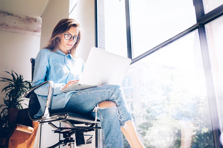 Hipster Girl use Laptop huge Loft Studio.Student Researching Process Work.Young Business Woman Working Creative Startup modern Office.Analyze market stock,new strategy.Blurred,film effect.Horizontal