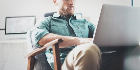 notebook design: Bearded Businessman work Laptop modern Design Interior Open Space Studio Office.Man sitting Vintage chair.Use contemporary Notebook, blurred background.Creative Process New Startup Idea.Closeup.Wide