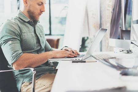 notebook design: Bearded Hipster working Laptop modern Interior Design Loft Office.Man Work Coworking Studio,Use contemporary Notebook,typing keyboard.Blurred Background.Creative Business Startup Idea.Horizontal,Film