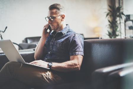 現代的なスマート フォン手 Calling.Blurred Background.Business スタートアップのアイデア Process.Film 効果を使用して、ラップトップのモダンなインテリア デザインのロフト Office.Man 仕事ヴィンテージ ソファーを機能成功のリスク マネージャー 写真素材 - 59133838