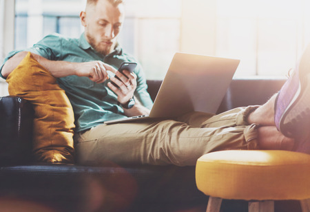 device: Bearded Hipster working Laptop modern Design Interior Studio Loft.Men work Vintage Sofa,Use Contemporary Notebook,Touching Smartphone.Blurred Background.Creative Business Startup Idea.Film flare