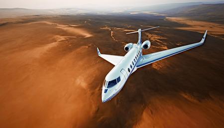 Draufsicht-Foto-weißes exklusives generisches Design Airplane.Private Jet, der die große Höhe kreuzt, fliegend über Berge. Leerer blauer Himmel mit Sun-Hintergrund. Geschäftsreise-Konzept. Horizontal. 3D-Rendering