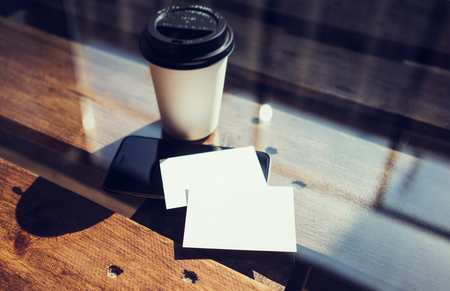 two object: Two Blank White Business Card Mockup Wood Table Take Away Coffee Cup Coworking.Modern Phone Ready Work Office Glass Background.Clean Object Private Corporate Information.Horizontal Hot Drinks Mock Up