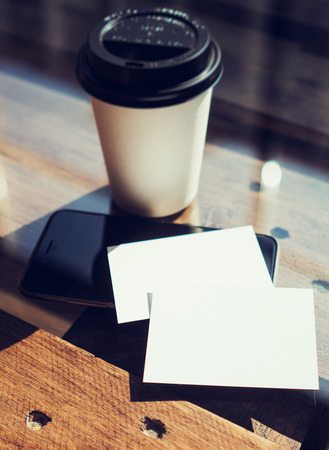 two object: Two Blank White Business Card Mockup Wood Table Take Away Coffee Cup Coworking.Modern Phone Ready Work Office Blurred Background.Clean Object Private Corporate Information.Vertical Hot Drinks Mock Up
