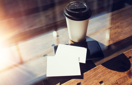 two object: Two Blank White Business Card Mockup Wood Table Take Away Coffee Cup Coworking.Modern Phone Ready Work Office Glass Background.Clean Object Private Corporate Info.Horizontal Hot Beverages Mock Up