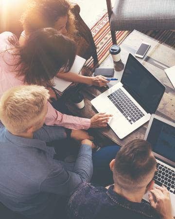 Groep jonge collega's maken van grote zakelijke beslissingen. Creatieve team discussie Collectieve werk Concept moderne kantoor. Start marketing idee presentatie. Vrouw aanraken digitale Laptop. Bovenaanzicht. Verticale